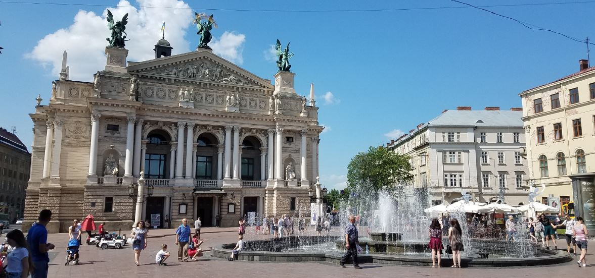 scene of square with fountain, statues and people of all ages. Large buildings surround the square and there is a cafe with umbrellas to one side.