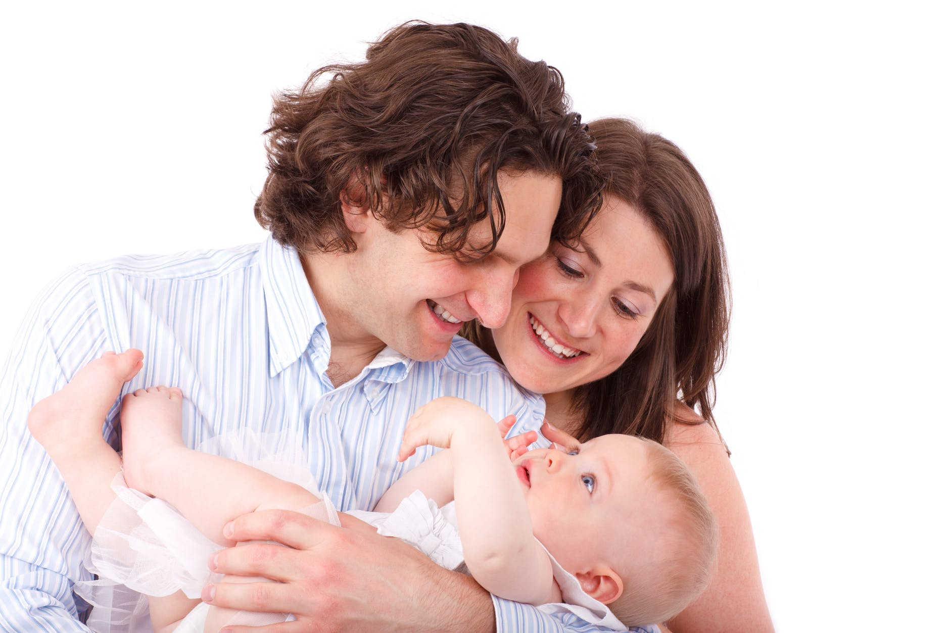 father holding infant child with mother resting her head on father's shoulder looking at baby