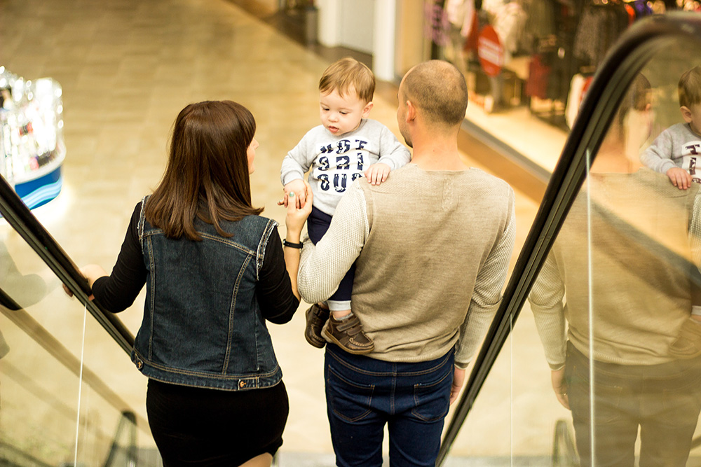 younc couple with child descending escalator