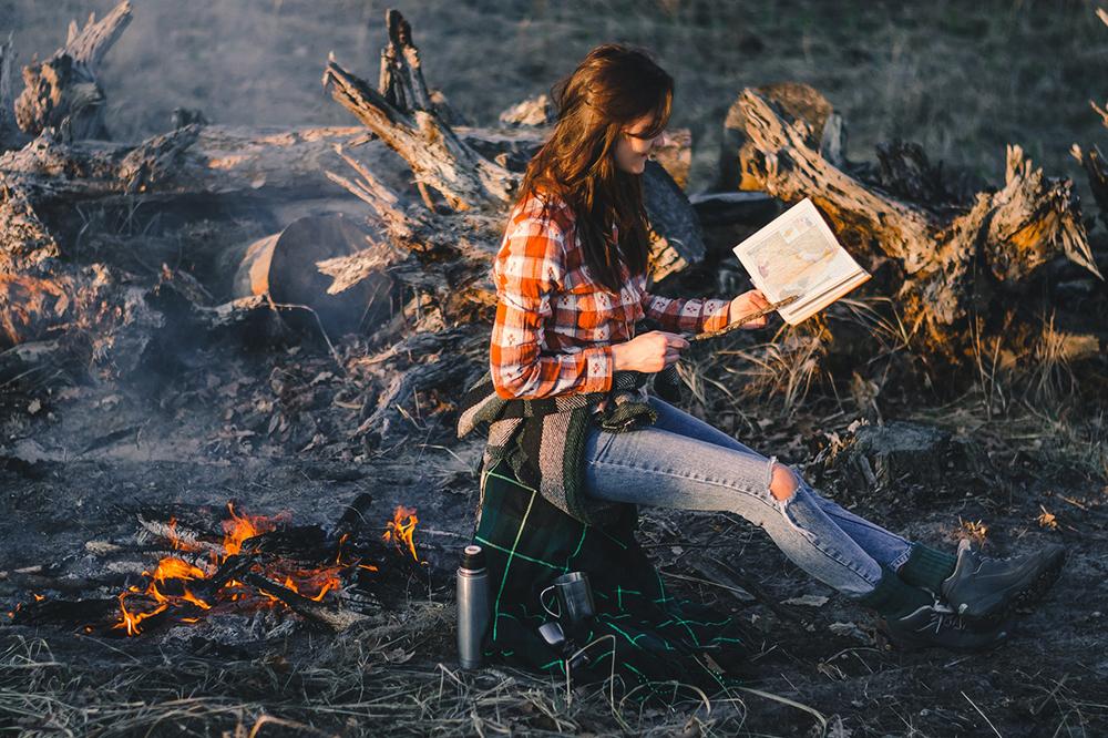 woman stiing near campfire