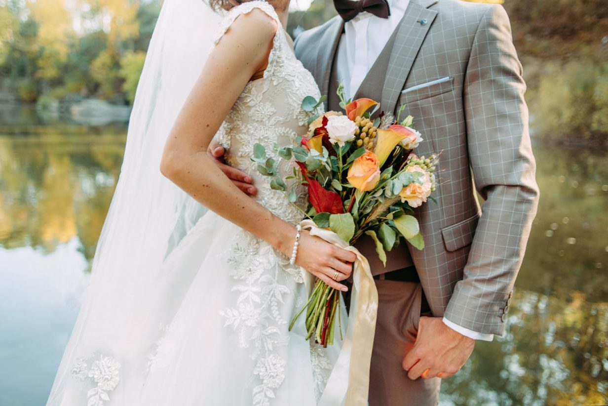 man in tuxedo and woman in wedding dress, holding flowers