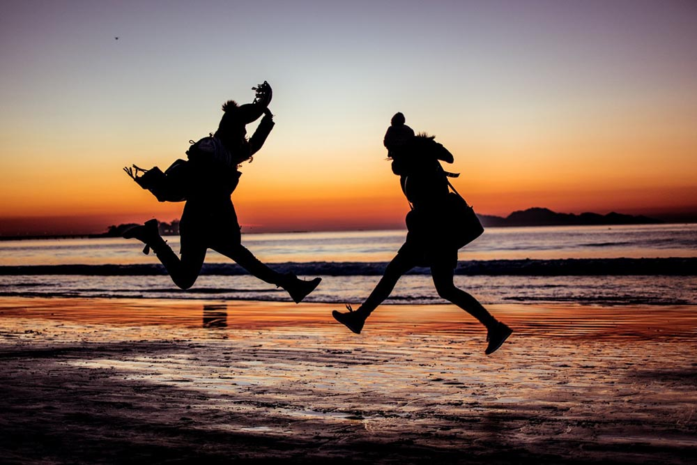 two people in silhouette jumping on the beah