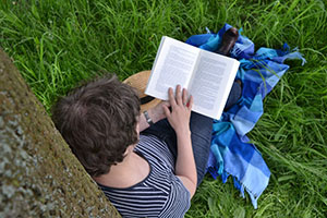 man leaning against a tree reading