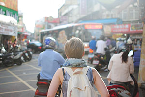 blonde woman with backpack in city with signs in Chinese